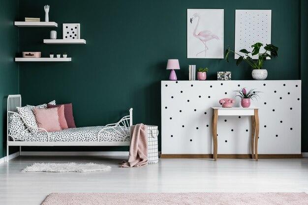 Różowa poduszka na wzorzystym łóżku w zielonym wnętrzu sypialni z plakatami na ścianie