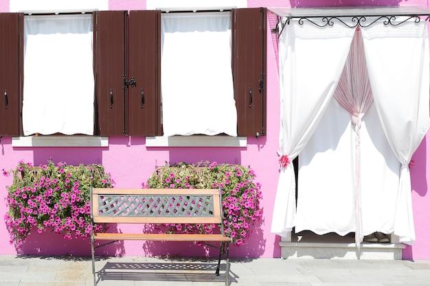 Różowa pomalowana ściana z dwoma oknami z drewnianymi okiennicami i drzwiami zasłoniętymi zasłoną na parapecie, doniczkowa z kwiatami, na wyspie burano, wenecja, włochy