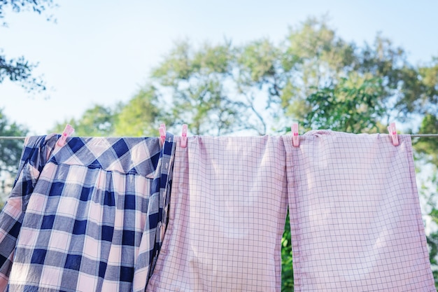 Różowa pościel i koszula suszą się na sznurze na zewnątrz.