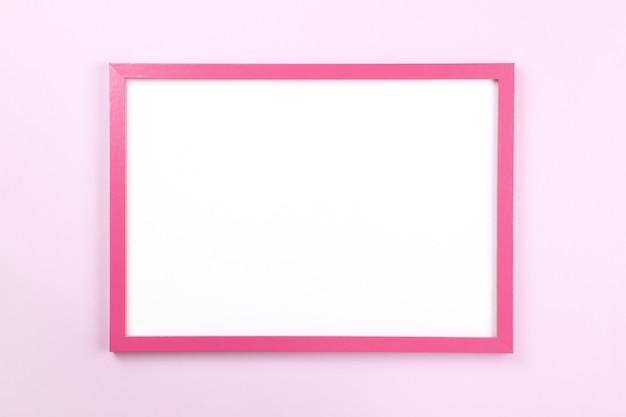 Różowa prostokątna ramka z pustym czystym białym środkiem na pastelowym różowym tle