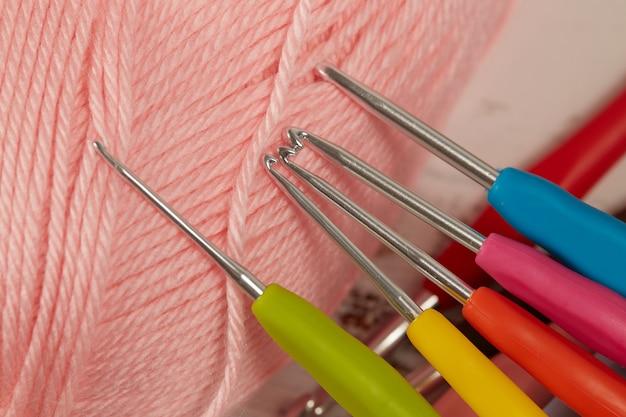 Różowa przędza i kolorowe szydełko z bliska.
