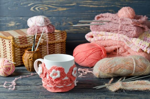 Różowa przędza i przedmioty rzemieślnicze na drewnianym stole