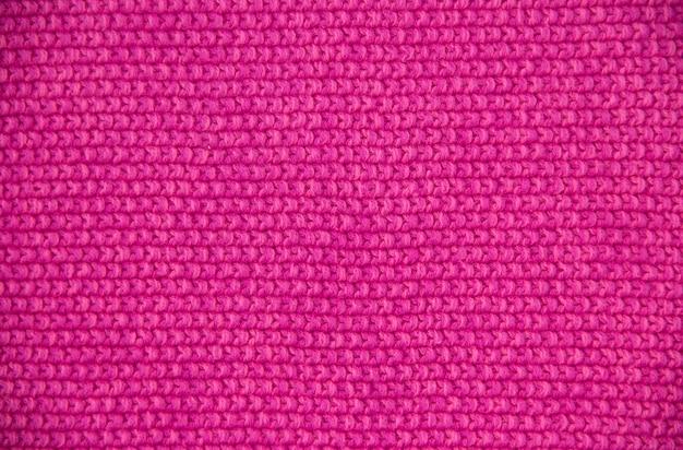Różowa przędza wełniana o dzianej fakturze. dzianie ręczne. ścieśniać. różowe tło.