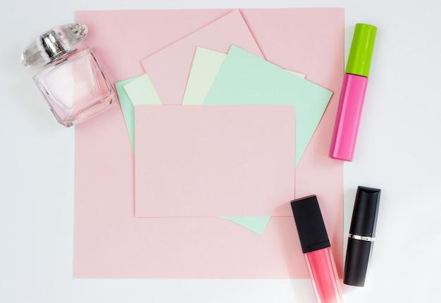 Różowa pusta karta, arkusz do pisania. układ dodawania tagów perfumami i szminką. widok z góry, leżał płasko, miejsce