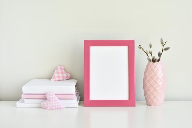Różowa pusta rama na białym stole z pastelowymi różowymi detalami.