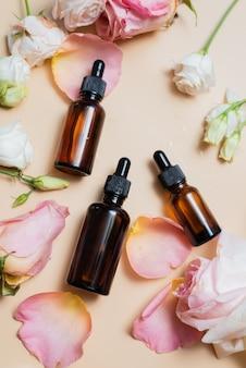 Różowa róża i szklane butelki kosmetyczne z zakraplaczem