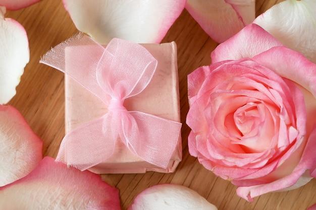 Różowa róża, płatki i prezent pudełko na podłoże drewniane