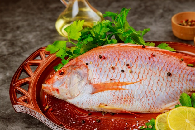Różowa ryba tilapia z ziołami i cytryną na tacy. ścieśniać.