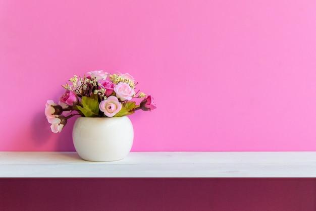 Różowa ściana z kwiatem na szelfowym białym drewnie, kopii przestrzeń dla teksta. martwa natura koncepcja