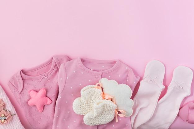 Różowa ściana z ubraniami, skarpetkami i zabawkami dla noworodka.