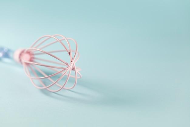 Różowa silikonowa trzepaczka z jasną rączką na niebieskim tle, z bliska