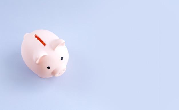Różowa skarbonka na szarym biurowym widoku z góry koncepcja oszczędzania pieniędzy
