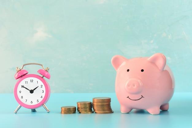 Różowa skarbonka obok małego budzika i trzech stosów monet
