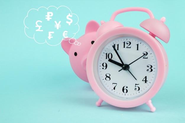 Różowa skarbonka w kształcie świni z cyfrowym hologramem walut świata w chmurze myśli nad głową na niebieskim tle. czas na oszczędzanie światowych walut.