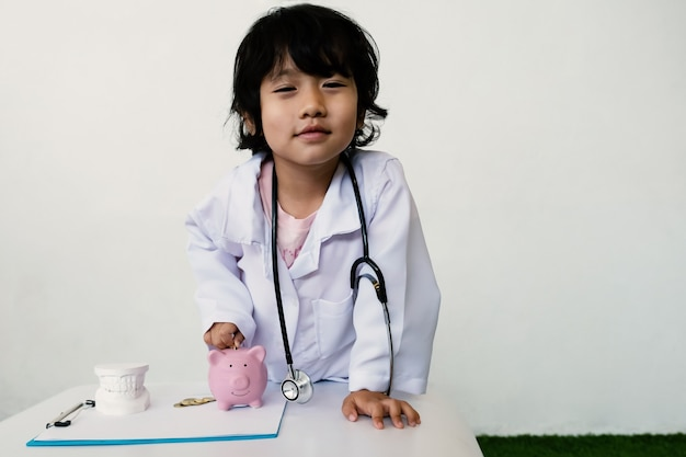 Różowa skarbonka z lekarzem dla dzieci i sprzętem medycznym oszczędność pieniędzy na koncepcję przyszłego planu
