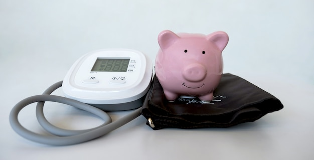 Różowa skarbonka z monitorem ciśnienia krwi na białym tle oszczędność pieniędzy na koncepcję przyszłego planu