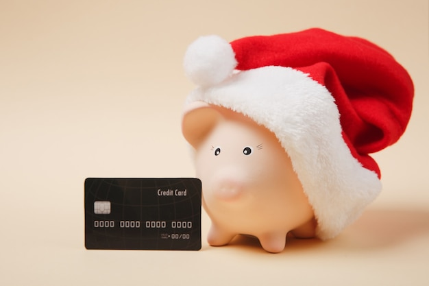 Różowa skarbonka z świątecznym kapeluszem, czarna karta kredytowa na białym tle na beżowym tle. akumulacja pieniędzy, inwestycje, usługi bankowe lub biznesowe, koncepcja bogactwa. skopiuj makiety reklamowe.