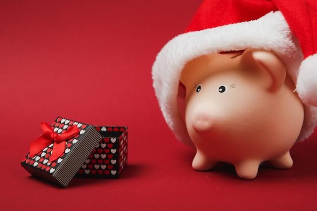 Różowa skarbonka z świątecznym kapeluszem, obecne pudełko z wstążką prezent na białym tle na czerwonym tle. akumulacja pieniędzy, inwestycje, koncepcja bogactwa. szczęśliwego nowego roku, wakacje urodzinowe. makieta miejsca na kopię.