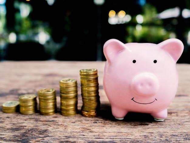 Różowa skarbonka z wykresem wzrostu stosu złotych monet, oszczędzając pieniądze na przyszły plan inwestycyjny i koncepcję funduszu emerytalnego.