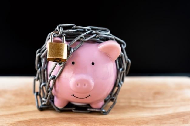 Różowa Skarbonka Zablokowana, Przykuta Czarnym Tłem, Chroń Oszczędności, Chroń Kapitał, Chroń Koncepcję Funduszu Emerytalnego. Premium Zdjęcia