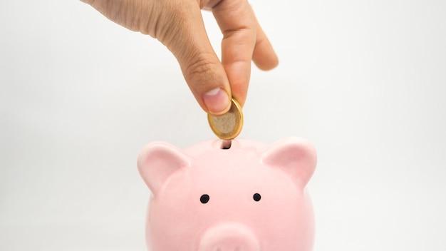 Różowa skarbonka zapisz monetę na białym tle zaoszczędź czas na monety, pieniądze i koncepcję biznesową