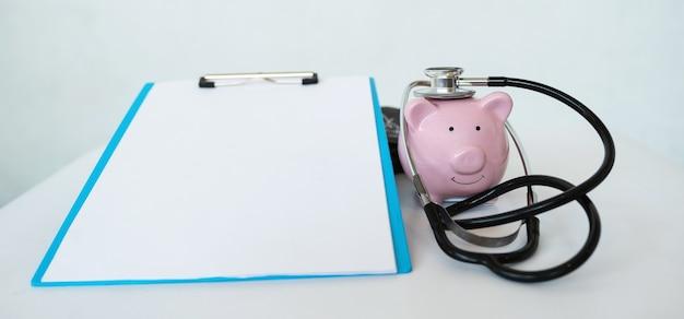 Różowa skarbonka ze stetoskopem i schowkiem na białym tle oszczędność na koncepcję przyszłego planu
