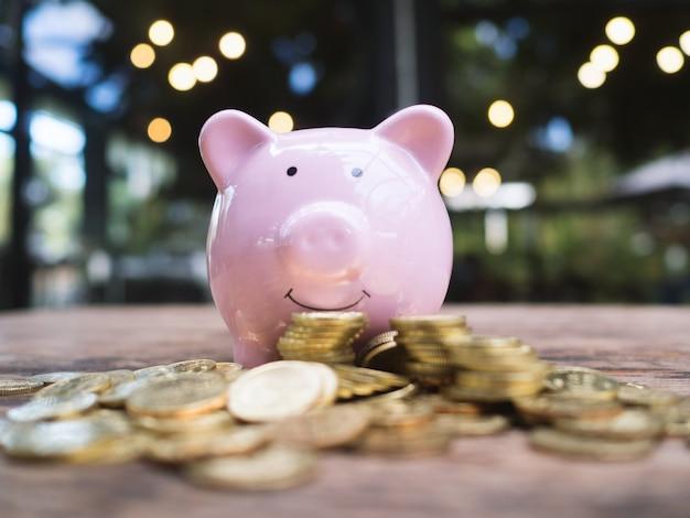 Różowa skarbonka ze stosem złotych monet, oszczędzając pieniądze na przyszły plan inwestycyjny i koncepcję funduszu emerytalnego.
