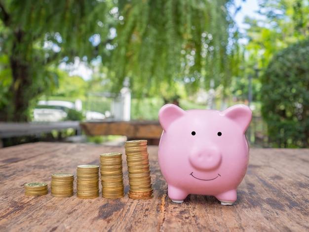 Różowa skarbonka ze stosem złotych monet oszczędzanie pieniędzy na przyszły plan i koncepcję funduszu emerytalnego