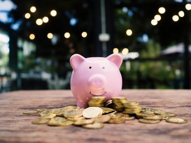 Różowa skarbonka ze stosem złotych monet oszczędzanie pieniędzy na przyszły plan inwestycyjny i fundusz emerytalny