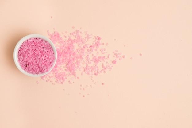 Różowa sól do kąpieli w białej misce z kryształkami rozsypanymi na brzoskwiniowym tle