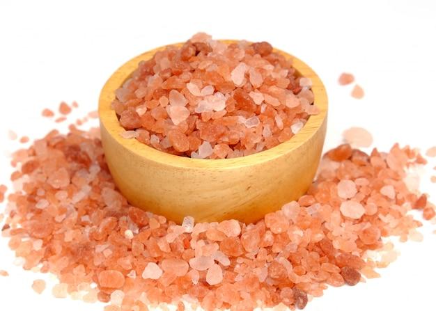 Różowa sól himalajska na drewnianej misce na białym tle