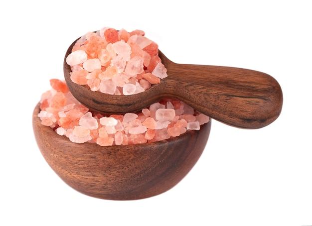 Różowa sól himalajska w drewnianej misce i łyżką, na białym tle