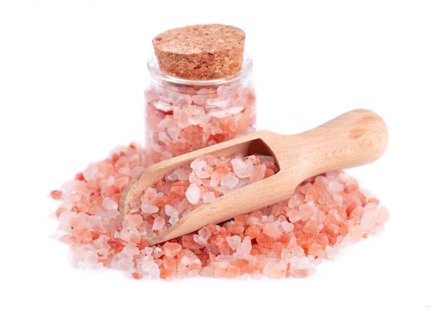 Różowa sól himalajska w szklanym słoju na białym tle