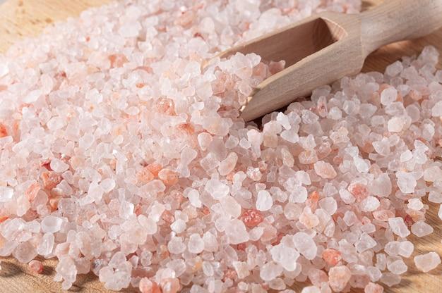Różowa sól himalajska. zbliżenie himalajskiej różowej soli kamiennej w drewnianej łyżce na czarnym tle. widok z góry