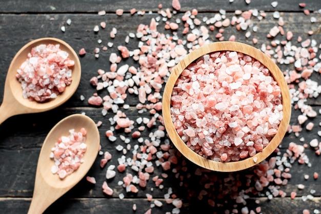 Różowa sól w drewnianej misce, położona na czarnym drewnie, sól himalajska.