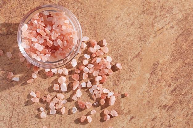 Różowa sól w szklanej misce na kamiennym tle, widok z góry