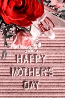 Różowa tablica filcowa z białymi cytatami happy mother's day i kwitnącymi kwiatami, widok z góry.