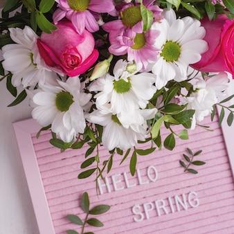 Różowa tablica z cytatem hellow spring i delikatnym kwitnącym bukietem kwiatów. widok z góry. świąteczna kartka z życzeniami.