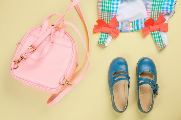 Różowa torba z kolorową sukienką i butami
