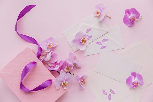 Różowa torebka prezentowa i latające kwiaty orchidei na jasnoróżowej powierzchni. karta z pozdrowieniami z widokiem z góry z delikatnymi kwiatami. wakacje, dzień kobiet, koncepcja pozdrowienia dzień matki.