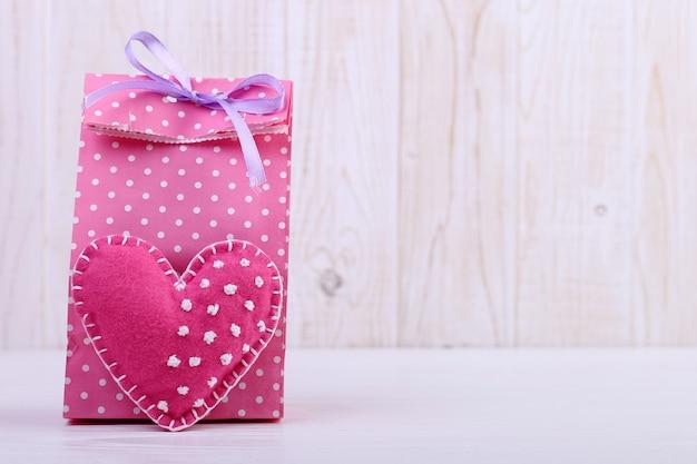 Różowa torebka w kropki i ręcznie robione serce z filcu. koncepcja dzień kobiet, baner, miejsce, puste.