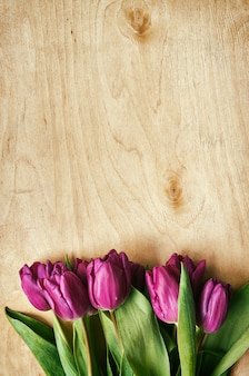 Różowa, tulipanowa wiązka na lekkim sklejkowym tle