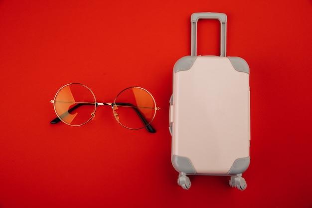 Różowa walizka na kółkach i żółte okulary na czerwonym tle. koncepcja podróży.