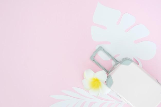 Różowa walizka podróżna na różowo z tropikalnymi liśćmi
