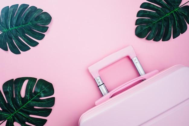 Różowa walizka z liśćmi palmowymi na różowym pastelowym kolorze dla koncepcji podróży