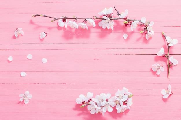 Różowa wiśnia kwitnie na drewnianym tle