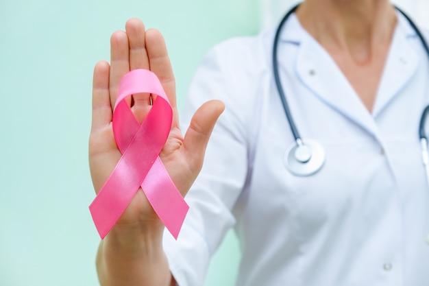 Różowa wstążka do świadomości raka piersi w ręce lekarza, kampania na temat raka piersi u kobiet.