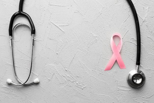 Różowa wstążka i czarny stetoskop na tynku