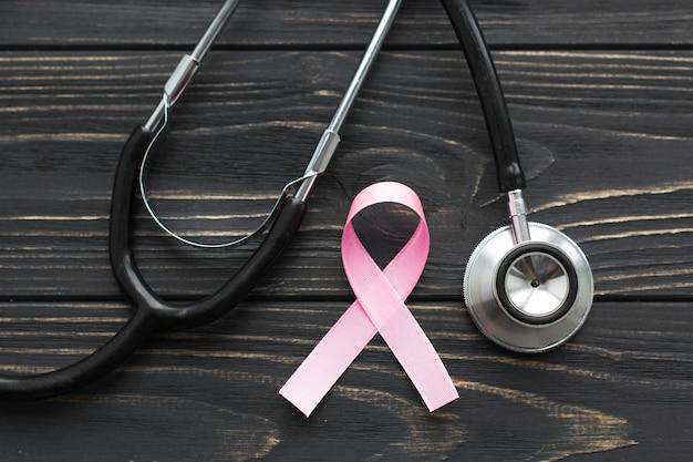 Różowa wstążka i stetoskop na ciemnym tle