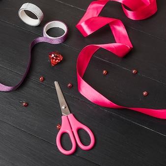 Różowa wstążka; kolorowa taśma klejąca; perły; diament i nożyczek na czarny drewniany stół